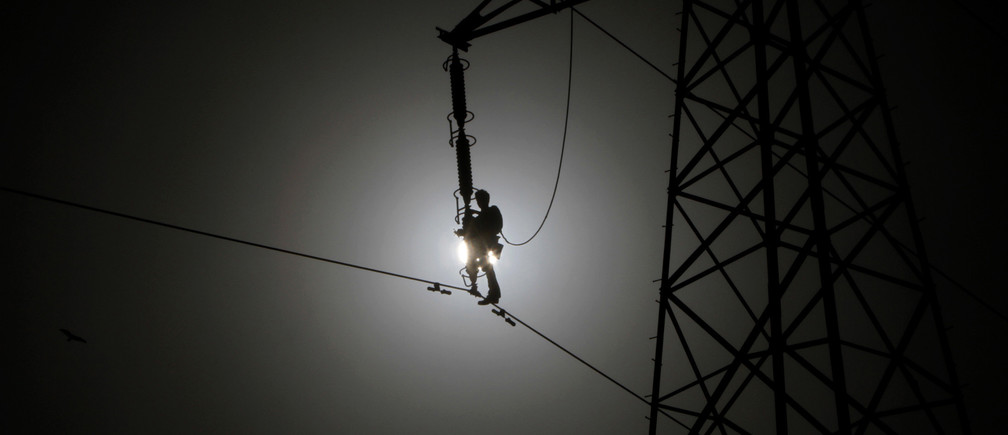 A technician is silhouetted as he works on power lines supplying electricity in Karachi July 30, 2011