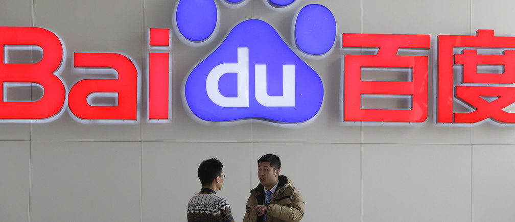 People talk in front of a Baidu's company logo at Baidu's headquarters in Beijing January 16, 2014. China's Baidu Inc knows where you are, where you're going and when you want dumplings, guiding you from web page to restaurant when you use its search engine.