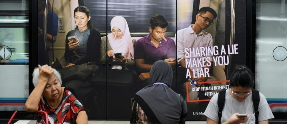 Commuters sit in front of an advertisement discouraging the dissemination of fake news, at a train station in Kuala Lumpur, Malaysia March 28, 2018. Picture taken March 28, 2018.