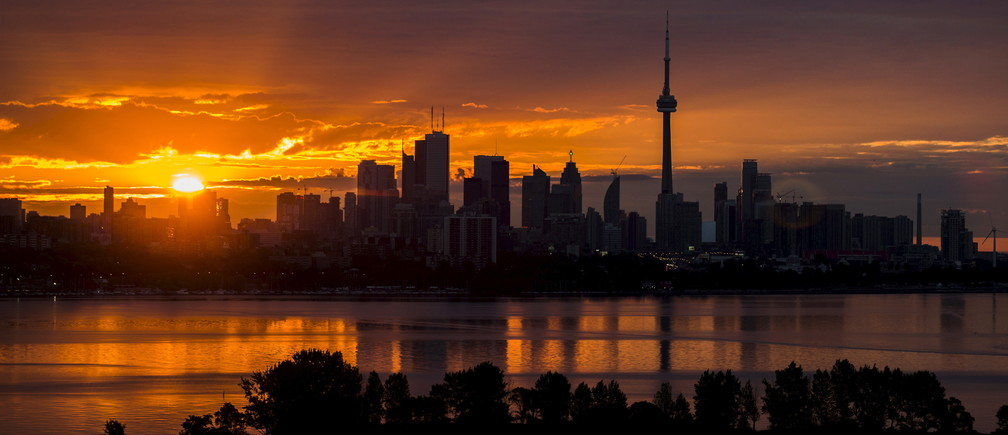 The sun rises over the skyline in Toronto, August 4, 2015.