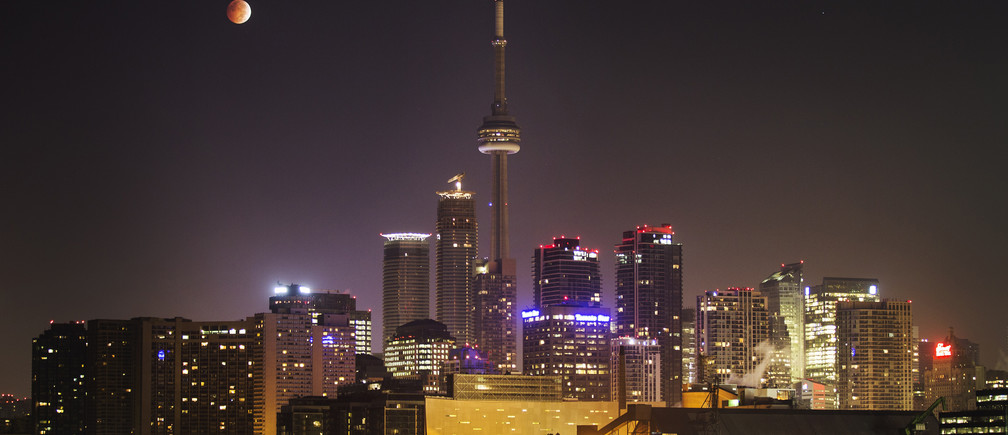 """The moon turns orange during a total lunar eclipse behind the CN Tower and the skyline during moonset in Toronto October 8, 2014. The eclipse is also known as a """"blood moon"""" due to the coppery, reddish color the moon takes as it passes into Earth's shadow. The total eclipse is the second of four over a two-year period that began April 15 and concludes on Sept. 28, 2015. The so-called tetrad is unusual because the full eclipses are visible in all or parts of the United States, according to retired NASA astrophysicist Fred Espenak.   REUTERS/Mark Blinch (CANADA - Tags: SOCIETY ENVIRONMENT CITYSCAPE TPX IMAGES OF THE DAY) - GM1EAA81KI601"""