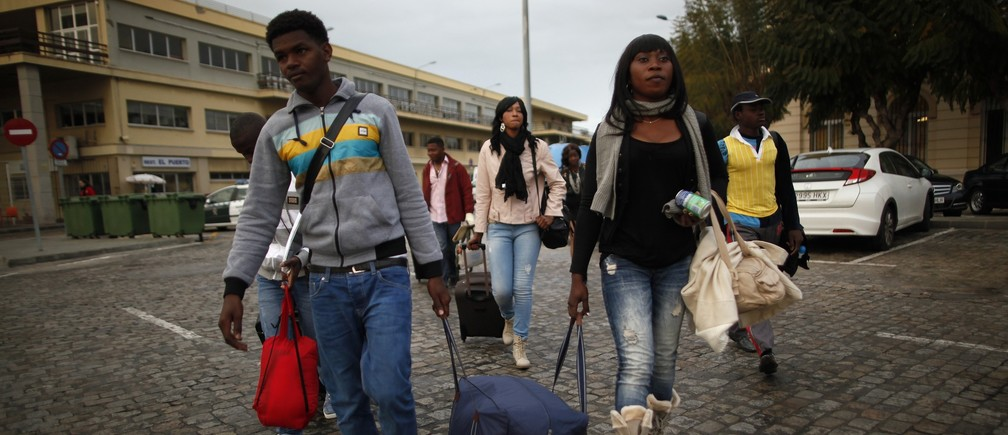 African migrants walk with their luggage after arriving from Melilla on a passenger ferry at Malaga port, southern Spain, April 3, 2014.