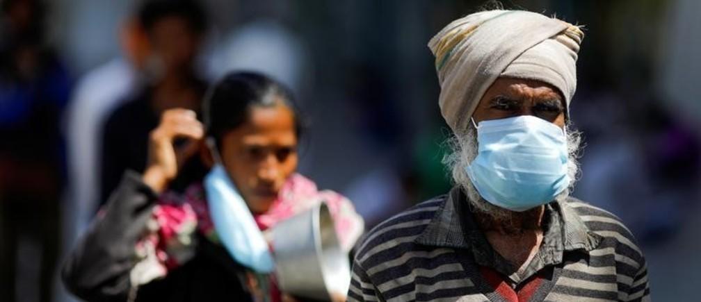 Des personnes portant des masques de protection font la queue pour obtenir de la nourriture à l'intérieur d'un complexe sportif transformé en refuge à New Delhi, en Inde.