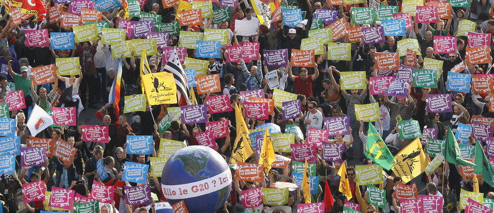 """General view as anti G20 demonstrators hold up signs near a sphere decorated as the planet with the message, """"Hello, the G20?"""" as they take part in a protest march against globalisation in Nice, southeastern France, November 1, 2011. G20 leaders will gather in Cannes for the final Summit of France's presidency November 3-4.      REUTERS/Eric Gaillard (FRANCE  - Tags: POLITICS BUSINESS) - RTR2THI1"""