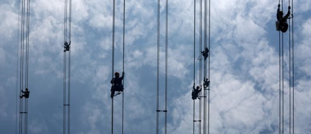 Workers of grid operator China Southern Power Grid inspect power cables connecting transmission towers in Dongguan, Guangdong province, China May 29, 2018. Picture taken May 29, 2018. REUTERS/Stringer  ATTENTION EDITORS - THIS IMAGE WAS PROVIDED BY A THIRD PARTY. CHINA OUT.     TPX IMAGES OF THE DAY - RC1636428C00