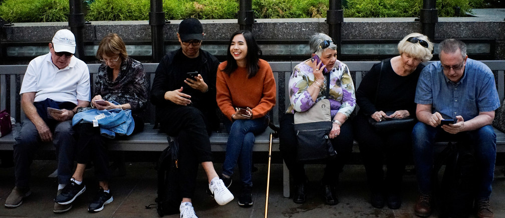 People look at their smartphones at the Rockefeller center in New York City, U.S., May 8, 2019. REUTERS/Eduardo Munoz - RC1EED1117E0