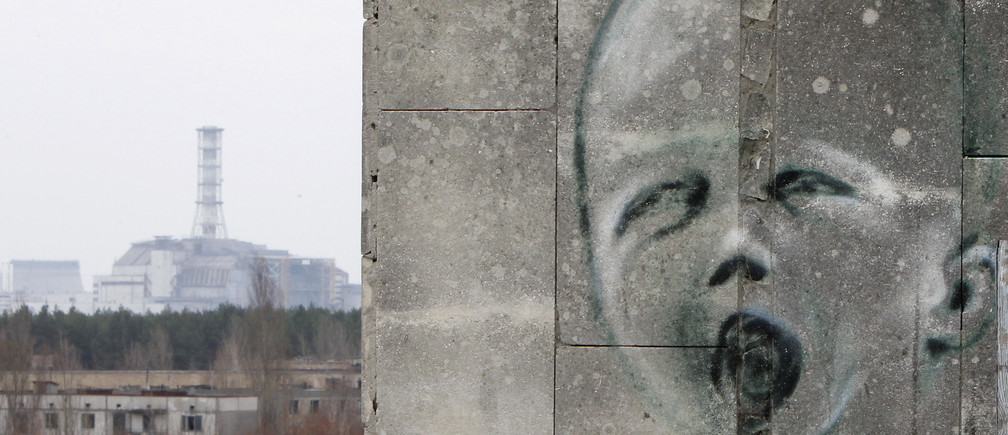 The sarcophagus covering the damaged fourth reactor at the Chernobyl nuclear power plant is seen behind a building decorated with a graffiti in the abandoned city of Prypiat April 4, 2011. Belarus, Ukraine and Russia will mark the 25th anniversary of the nuclear reactor explosion in Chernobyl, the place where the world's worst civil nuclear accident took place, on April 26. Engineers are still struggling to regain control of damaged reactors at the Fuskushima plant after last month's earthquake and tsunami, in the worst nuclear crisis since Chernobyl in 1986, with the government urging the operator of the plant to act faster to stop radiation spreading.    REUTERS/Gleb Garanich  (UKRAINE - Tags: ANNIVERSARY DISASTER ENERGY ENVIRONMENT IMAGES OF THE DAY) - GM1E74500L501