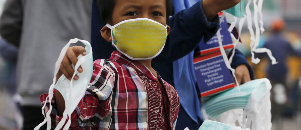 A child offers face masks to people along a haze shrouded street in Palembang, on the Indonesian island of Sumatra, September 20, 2015.  Indonesia will take 30 days to bring smouldering forest fires under control, the national disaster management agency said on Friday, as smog from the fires pushes pollution in Southeast Asia to record highs.  REUTERS/Beawiharta - RTS1XYP