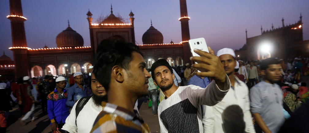 A Muslim man takes a selfie after eating his iftar (breaking fast) meal during the holy month of Ramadan at the Jama Masjid (Grand Mosque) in the old quarters of Delhi, India, May 20, 2018. REUTERS/Adnan Abidi - RC17179E9E00