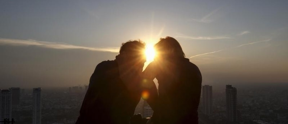 A couple enjoy the sunset on the roof top of an building in Bangkok April 19, 2015.