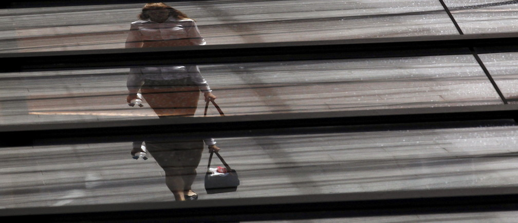 An office worker with a shopping bag is reflected on the roof of a building in central Sydney February 5, 2013. Picture rotated 180 degrees.  REUTERS/Daniel Munoz/File Photo - GF10000390441