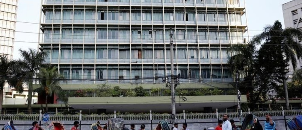 Commuters walk in front of the Bangladesh central bank building in Dhaka, Bangladesh, September 30, 2016. Picture taken September 30, 2016. REUTERS/Mohammad Ponir Hossain