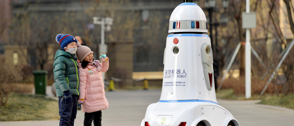 Children react next to a security robot patrolling inside a residential compound in Hohhot, Inner Mongolia, China January 18, 2019. REUTERS/Stringer  ATTENTION EDITORS - THIS IMAGE WAS PROVIDED BY A THIRD PARTY. CHINA OUT.          TPX IMAGES OF THE DAY - RC1FFD599740