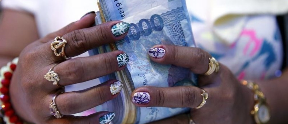 """A casino financier wearing rings and with painted fingernails, counts money she collected from a gambler only moments before, in Angeles city, north of Manila, Philippines, May 25, 2015. Financiers normally loan money with high interest rates to gamblers inside casinos. The Philippines has emerged as one of Asia's hottest gambling hubs after it launched its 120-hectare (1.2 square km) gaming and leisure enclave called Entertainment City in the capital, modelled on the Las Vegas strip. When paying your final respects for a relative or friend, the last thing you might expect to see at the wake is people placing bets on a card game or bingo. Not in the Philippines. Filipinos, like many Asians, love their gambling. But making wagers on games such as """"sakla"""", the local version of Spanish tarot cards, is particularly common at wakes because the family of the deceased gets a share of the winnings to help cover funeral expenses. Authorities have sought to regulate betting but illegal games persist, with men and women, rich and poor, betting on anything from cockfighting to the Basque hard-rubber ball game of jai-alai, basketball to spider races. Many told Reuters photographer Erik De Castro that gambling is only an entertaining diversion in a country where two-fifths of the population live on $2 a day. But he found that some gamble every day. Casino security personnel told of customers begging to be banned from the premises, while a financier who lends gamblers money at high interest described the dozens of vehicles and wads of land titles given as collateral by those hoping lady luck would bring them riches.  REUTERS/Erik De Castro PICTURE 14 OF 29 FOR WIDER IMAGE STORY """"HIGH STAKES IN MANILA"""". SEARCH """"BINGO ERIK"""" FOR ALL IMAGES. - GF10000135849"""
