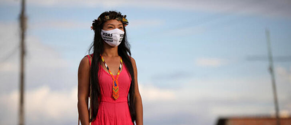 "Vanderlecia Ortega dos Santos, 32, a nurse from the Witoto tribe, an indigenous ethnic group, who has volunteered to provide the only frontline care protecting her indigenous community of 700 families from the COVID-19 outbreak, wears a face mask that reads ""Indigenous lives matter"" as she poses for a photo outside, near her home in Parque das Trios, during the coronavirus disease (COVID-19) outbreak, in the Taruma district, Manaus, Brazil, May 3, 2020.  ""Our people are dying from this disease here and they are not being recognized as indigenous people by the state and Sesai,"" said Santos. REUTERS/Bruno Kelly      SEARCH ""CORONAVIRUS INDIGENOUS NURSE"" FOR THIS STORY. SEARCH ""WIDER IMAGE"" FOR ALL STORIES."