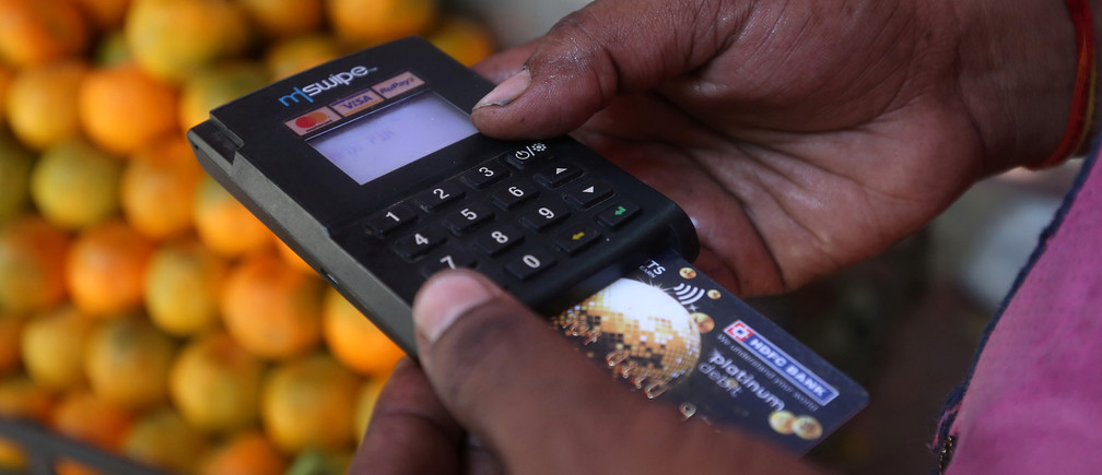 A fruit seller swipes a customer's debit card at a roadside market in Mumbai, India, April 2, 2019.