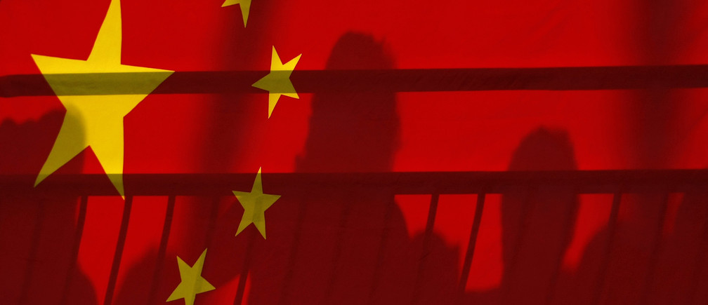 The shadows of spectators are seen through a Chinese national flag during the men's kayak (K1) semifinal at the Beijing 2008 Olympic Games August 12, 2008.     REUTERS/Phil Noble (CHINA) - BR2E48C0SY2EC