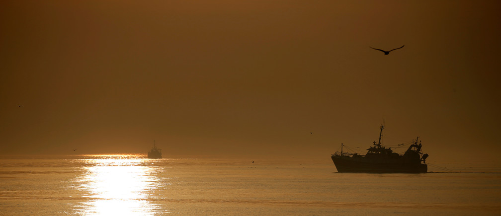 A Boulogne sur Mer based trawler is seen fishing during sunrise, off the coast of northern France, August 29, 2017