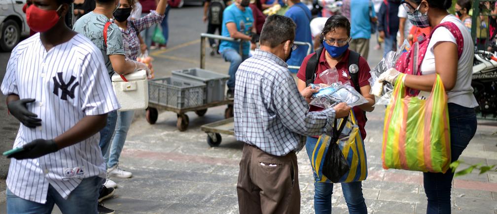 Los vendedores ambulantes ofrecen sus productos mientras otras personas caminan por la calle, ya que la ciudad permitió que algunos negocios reabrieran el miércoles después de una caída en las muertes diarias debido al brote de la enfermedad coronavirus (COVID-19), en Guayaquil, Ecuador, el 20 de mayo de 2020.