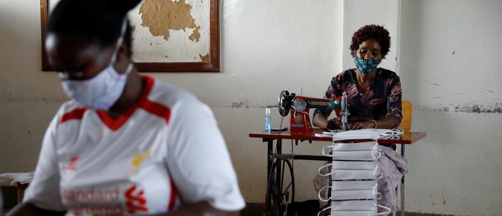 Mujeres utilizan máquinas de coser para fabricar máscaras faciales para ayudar a combatir la propagación de la enfermedad coronavirus (COVID-19) en el Centro Educativo Raila en los barrios marginales de Kibera en Nairobi, Kenya, 18 de abril de 2020.