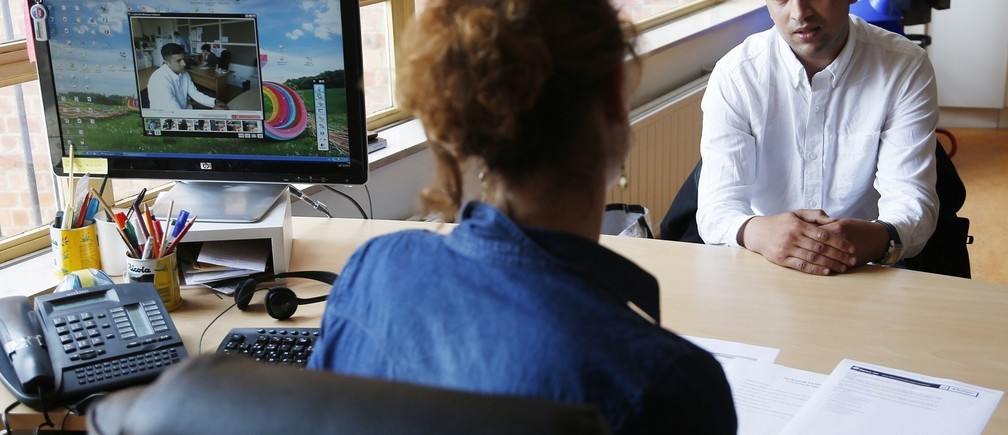 """Unemployed Belgian Mohamed Sammar (R) answers questions during a simulated job interview, which is recorded to help him get feedback afterwards in Brussels July 2, 2013. Sammar, 27, has been looking for a job in the construction sector for 2 years. """"Fit for a job"""" is the initiative of former Belgian boxing champion Bea Diallo, whose goal was to restore the confidence of unemployed people and help them find a job through their participation in sports. Picture taken July 2, 2013. REUTERS/Francois Lenoir (BELGIUM - Tags: SPORT BOXING SOCIETY BUSINESS EMPLOYMENT) - RTX11DQK"""