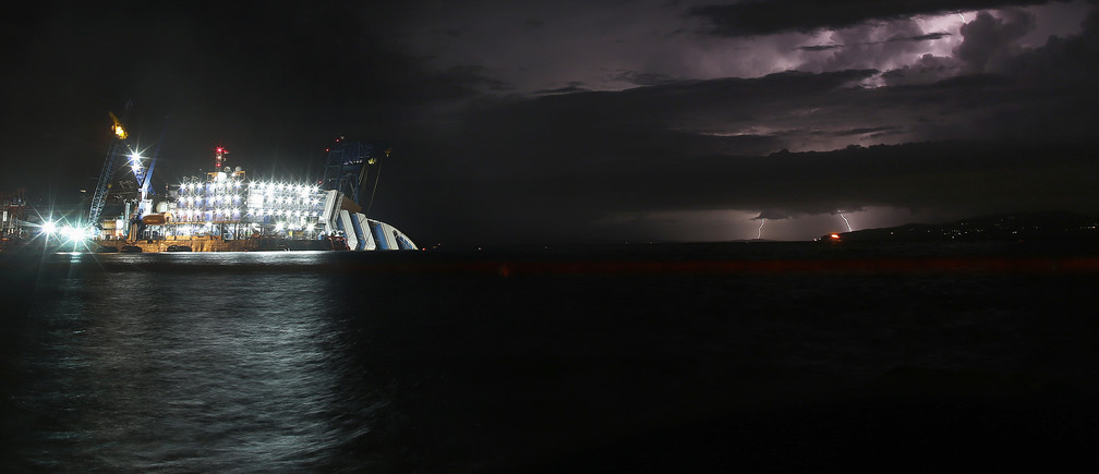 A lightning storm is pictured over the sea near the capsized cruise liner Costa Concordia lying surrounded by cranes outside Giglio harbour September 15, 2013. REUTERS/Tony Gentile (ITALY - Tags: DISASTER MARITIME ENVIRONMENT) - GM1E99G0I5501