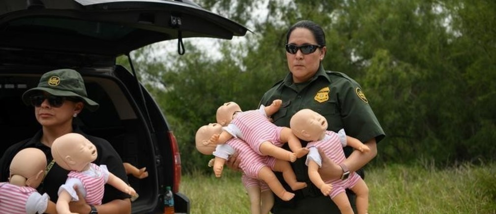 A U.S. Border Patrol agent holds infant dolls in preparation for a demonstration during a 'Border Safety Initiative' media event at the U.S.-Mexico border in Mission, Texas, U.S., July 1, 2019.  REUTERS/Loren Elliott     TPX IMAGES OF THE DAY - RC1587413480