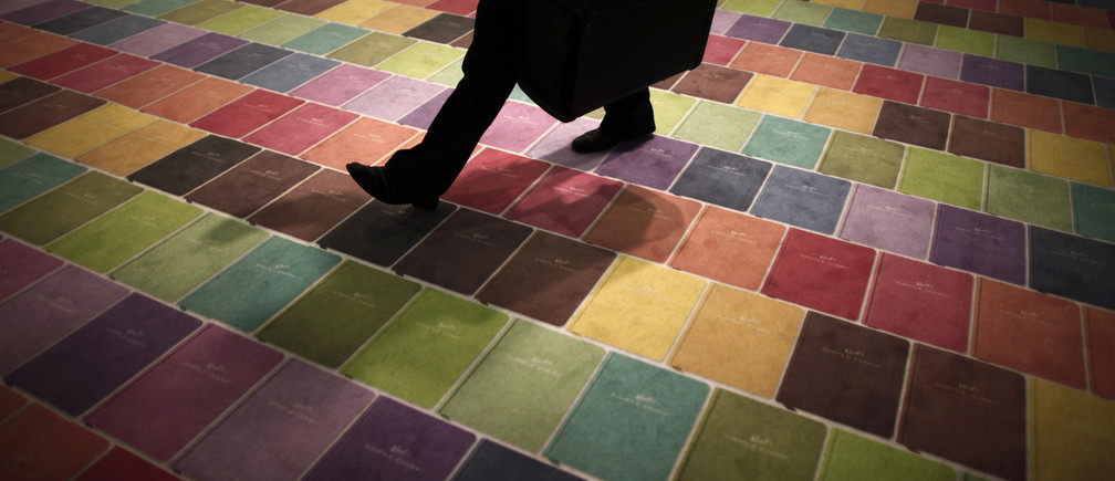 A man walks over a colourful carpet at an exhibition stand at the Frankfurt book fair October 16, 2009.