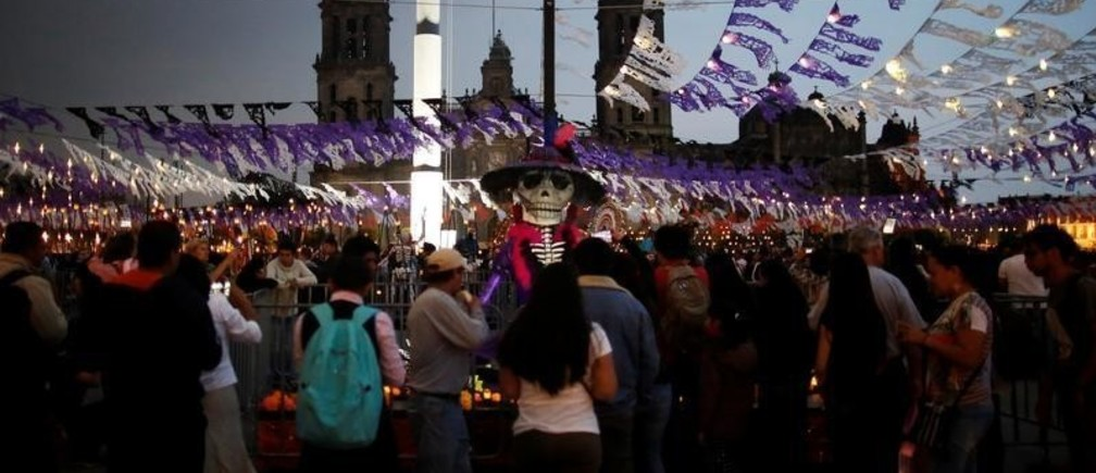 """People walk around an altar displaying a """"Catrina"""", a Mexican character also known as """"The Elegant Death,"""" as part for the upcoming annual Day of the Dead on November 1 and 2, at the Zocalo in Mexico City, Mexico October 30, 2017."""
