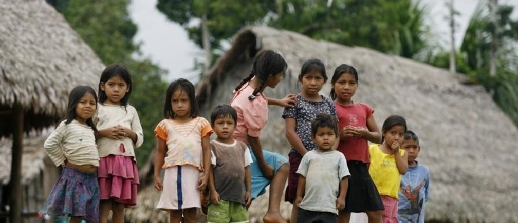 Children stand in a village along the edge of the Pacaya Samiria National Reserve, by the Maranon river in the Amazon jungle March 29, 2008. The Pacaya Samiria National Reserve is located in Peru's Amazon region, 93 miles (150 km) from Iquitos city. The reserve is the largest in Peru and the second largest in the Amazon region. The great size of the reserve assures that it will be ecologically and genetically representative of the region, with an abundance of virtually unchanged areas. Approximately 47,000 people live in the reserve and are located mainly along its edges in villages. REUTERS/Mariana Bazo (PERU) - GM1E43U0WSX01