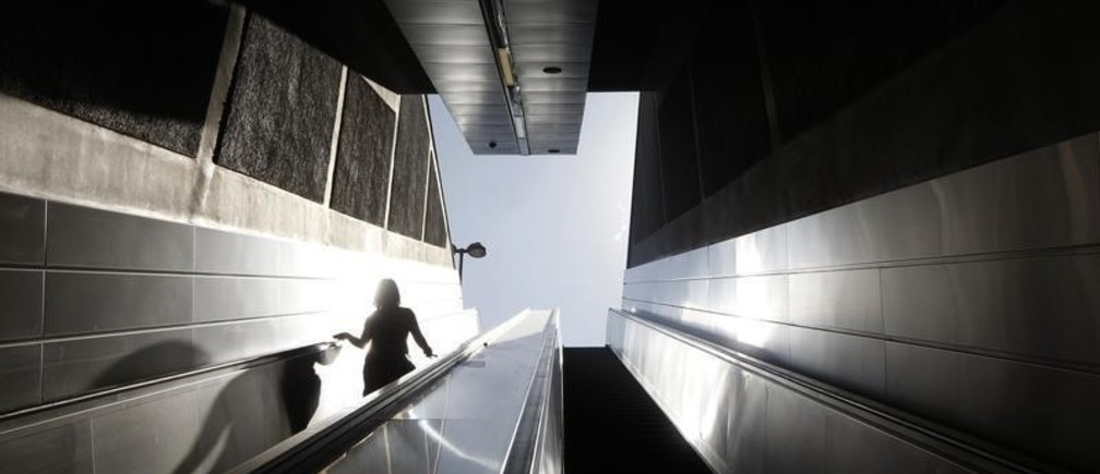 A woman walks down the stairs to the entrance of a closed metro station during a 24-hour transport strike in Athens, September 28, 2011.