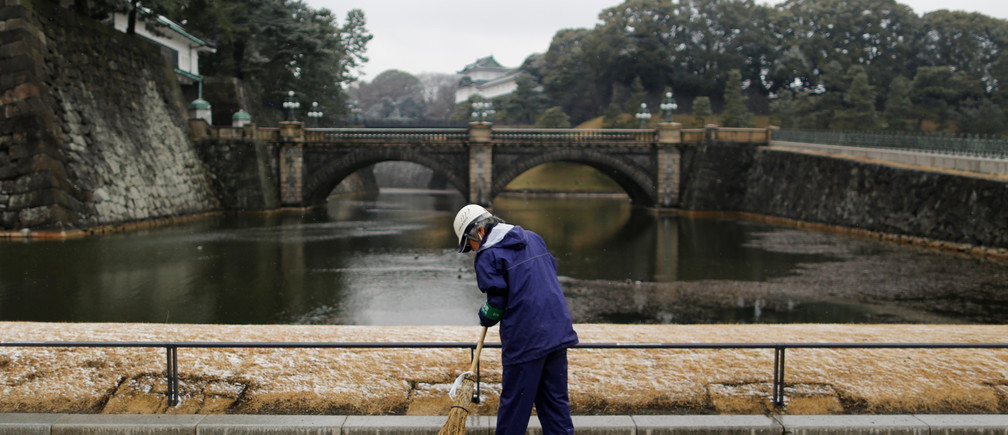 A worker cleans the compound at the Imperial Palace as snow falls in Tokyo, Japan February 9, 2019.  REUTERS/Issei Kato - RC1757701890