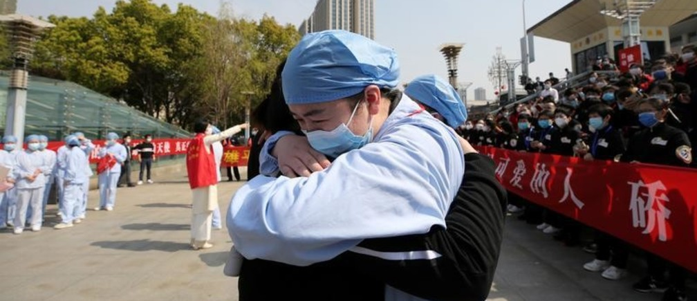 A local medical worker embraces and bids farewell to a medical worker from Jiangsu at the Wuhan Railway Station as the medical team from Jiangsu leaves Wuhan, the epicentre of the coronavirus disease (COVID-19) outbreak, in Hubei province, China March 19, 2020. China Daily via REUTERS  ATTENTION EDITORS - THIS IMAGE WAS PROVIDED BY A THIRD PARTY. CHINA OUT.     TPX IMAGES OF THE DAY - RC2WMF94JYMV