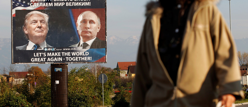 A woman passes a billboard showing a pictures of US president-elect Donald Trump and Russian President Vladimir Putin in Danilovgrad, Montenegro, November 16, 2016. REUTERS/Stevo Vasiljevic - RTX2TYXR