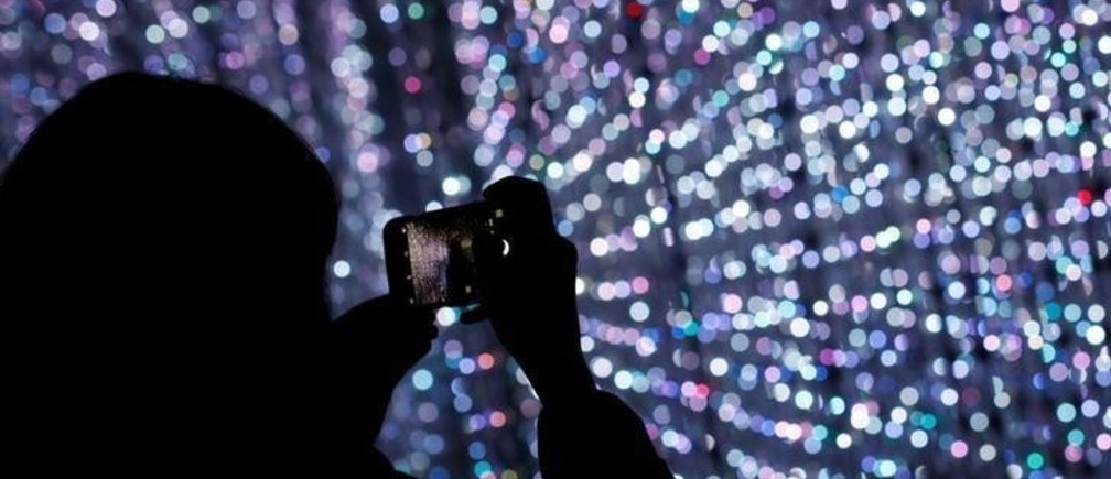"""A visitor takes photos at a digital installation which is a part of """"Dance! Art Exhibition, Learn & Play!"""" by Japanese group teamLab in Taipei, Taiwan January 16, 2017. REUTERS/Tyrone Siu"""