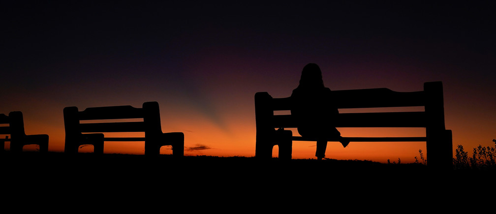 A women sits alone on a park bench watching the sky after sun set in Encinitas, California, U.S. October 7, 2019.       REUTERS/Mike Blake - RC153DF2FBA0