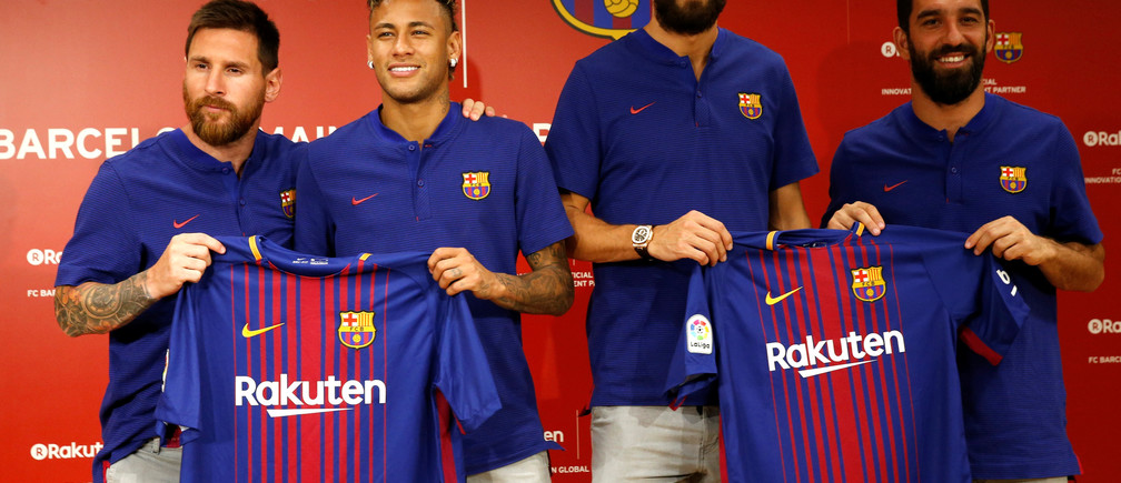 FC Barcelona players (L-R) Lionel Messi , Neymar, Gerard Pique and Arda Turan holding their uniforms pose for a photo during a news conference to announce the sponsorship deal between the team and Japanese e-commerce operator Rakuten Inc. in Tokyo, Japan July 13, 2017.  REUTERS/Kim Kyung-Hoon - RC1F6F314C70