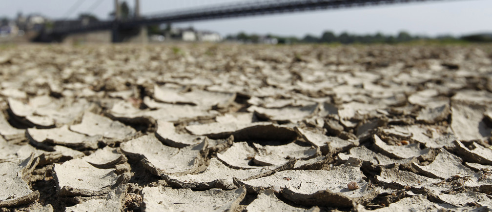 Cracked and dry earth is seen in the wide riverbed of the Loire River near the Anjou-Bretagne bridge in Ancenis, western France, May 20, 2011. The French environment minister said on Monday that France was in a 'situation of crisis' and on Wednesday imposed curbs on water consumption in a third of France's administrative departments.    REUTERS/Stephane Mahe (FRANCE - Tags: ENVIRONMENT) - PM1E75K0X8B01