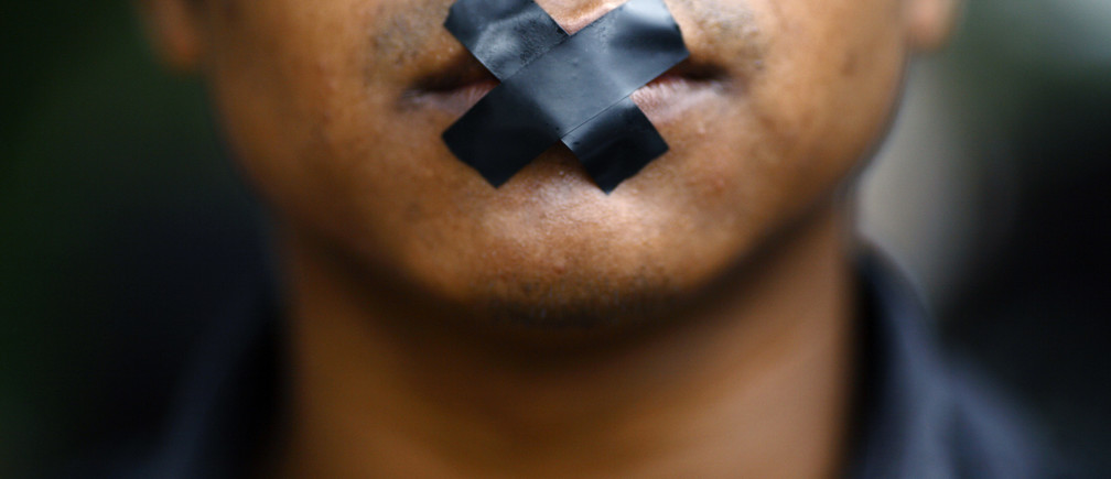 An artist, with his mouth taped, takes part in a protest demanding the safety of artist Manish Harijan and his freedom of expression, near the Kathmandu District Administration Office (DAO) in Kathmandu September 13, 2012. According to the local media, the protest was organized by Nepalese artists because of the death threat received by Harijan for creating and exhibiting paintings depicting Hindu gods blended into images of western superheroes like Ghost Rider and Superman. The Siddhartha Art Gallery, where the paintings are currently being exhibited at, has been sealed by the DAO. REUTERS/Navesh Chitrakar (NEPAL - Tags: RELIGION SOCIETY CIVIL UNREST) - GM1E89D1CDP01