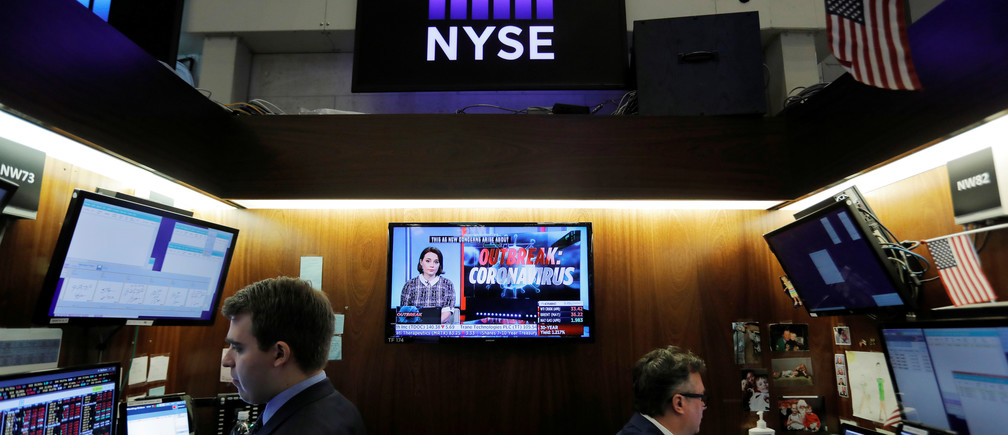 Coronavirus updates are seen on a news broadcast as traders work on the floor of the New York Stock Exchange (NYSE) in New York City, New York, U.S., March 11, 2020. REUTERS/Andrew Kelly - RC2RHF9B7F0Y