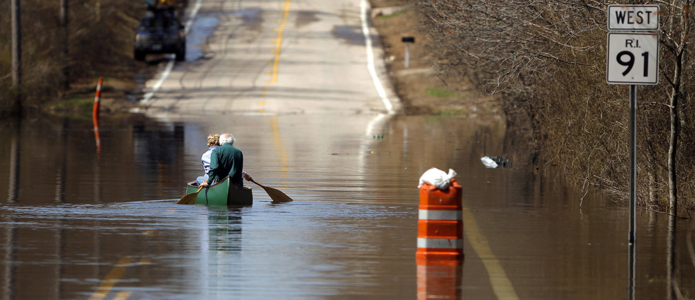 A couple canoes across a flooded section of road in Westerly, Rhode Island April 1, 2010. REUTERS/Brian Snyder (UNITED STATES - Tags: ENVIRONMENT TRANSPORT IMAGES OF THE DAY SOCIETY) - GM1E642036W01