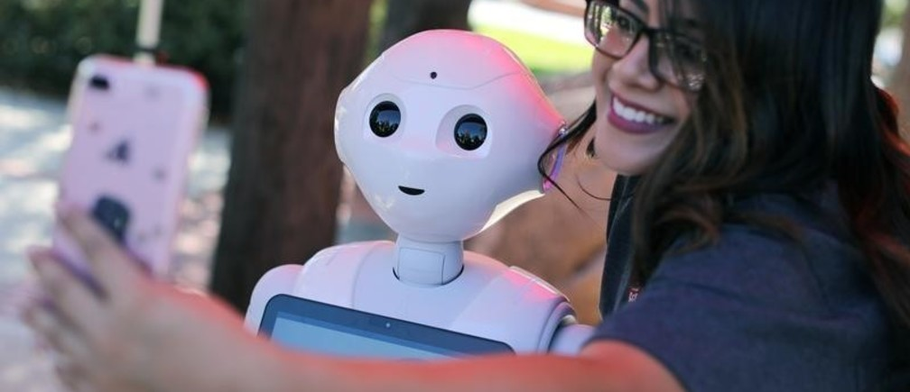 """San Marcos student Amaris Gonzalez takes a selfie with """"Pepper"""" an artificial Intelligence project utilizing a humanoid robot from French company Aldebaran and reprogramed as an assistant for students attending Palomar College in San Marcos, California, U.S. October 10, 2017. REUTERS/Mike Blake - RC1C5B9E1CA0"""