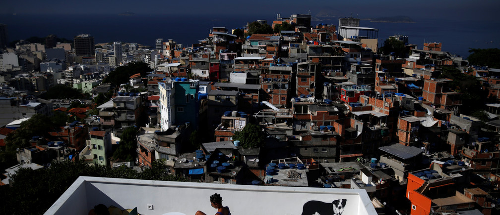 A woman sits on a terrace at Tiki hostel in Cantagalo favela, in Rio de Janeiro, Brazi