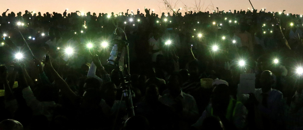 Sudanese demonstrators use their mobile phone torches as lamps as they attend a mass anti-government protest outside the Defence Ministry in Khartoum, Sudan, April 21, 2019. REUTERS/Mohamed Nureldin Abdallah - RC111A542C20