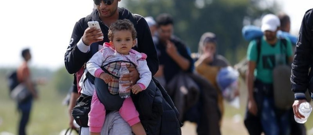 A migrant uses his mobile phone carrying his child as he walks through fields with others next to a collection point near the Serbian Hungarian border in Roszke, Hungary September 13, 2015.      REUTERS/Laszlo Balogh