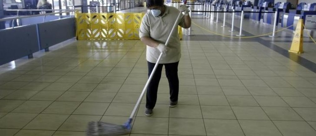 An airport cleaning lady mops the floor while protecting herself with a surgical mask against the swine flu in Panama City April 27, 2009. Panama's health department is on alert at the Tocumen international airport against the swine flu. REUTERS/Alberto Lowe (PANAMA HEALTH TRANSPORT)