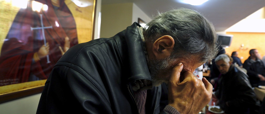 """A man prays before his lunch at the Orthodox church """"Galini"""" foundation soup kitchen in Athens, Greece in this March 19, 2015 file photo. To match Special Report EUROZONE-GREECE/NEGOTIATIONS     REUTERS/Yannis Behrakis/Files - GF10000139587"""