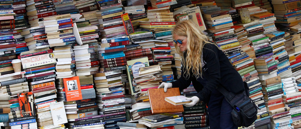 A woman arrange books at her open air book store in Skopje, Macedonia May 9, 2017. REUTERS/Ognen Teofilovski - RTS15WVK