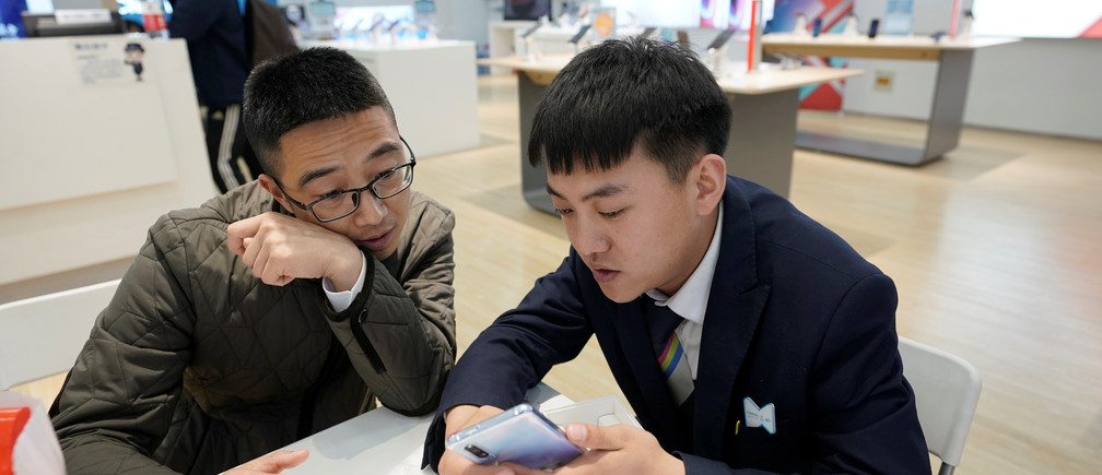 A salesman shows a new Huawei P30 smartphone to a customer after Huawei's P30 and P30 Pro went on sale at a Huawei store in Beijing, China, April 11, 2019. REUTERS/Jason Lee - RC1EF395EEB0