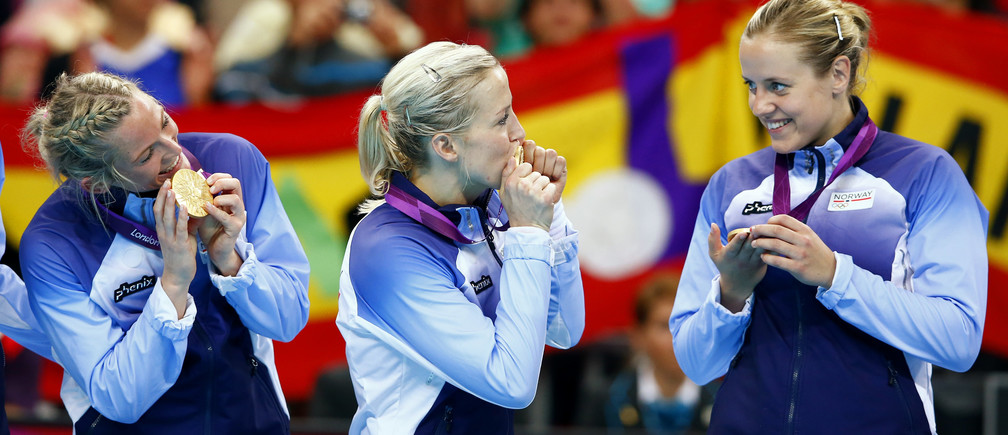 Members of Norway's winning team kiss their gold medals during the victory ceremony for the women's handball final during the London 2012 Olympic Games at the Basketball Arena August 11, 2012.